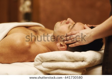 Close up portrait of a young man receiving head massage from a professional masseur at the spa center relaxation peacefulness pampering wellness wellbeing luxury massaging relaxing lifestyle #641730580