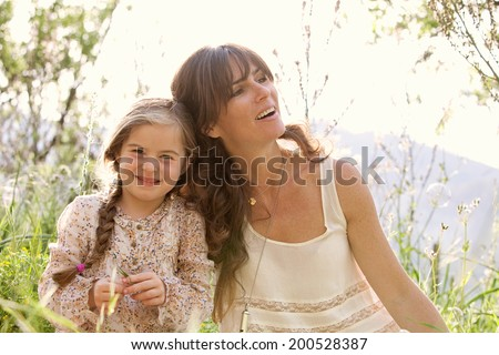 Close up portrait of a young mother and daughter relaxing during a sunny holiday, with their heads together joyfully smiling with fun expressions in a field. Family activities lifestyle, outdoors.