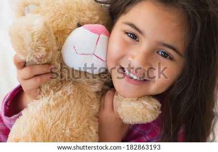 Close-up portrait of a young smiling girl with stuffed toy