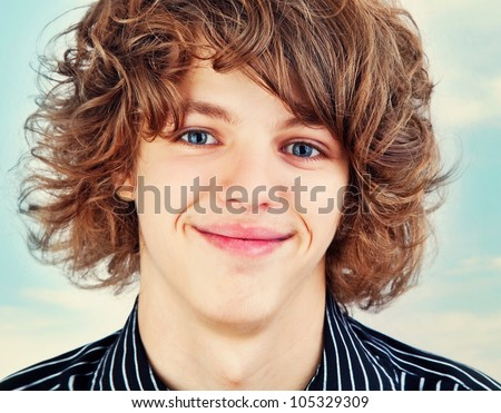 Close up portrait of a young smiling teen with curly hair .