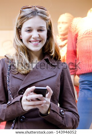 Close up portrait of a young stylish teenager woman using a smartphone device while visiting the city, leaning on a fashion store shop window while shopping for clothes.