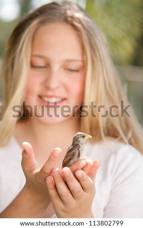 Close up portrait of a young teenage girl holding a baby bird in her hands, smiling.