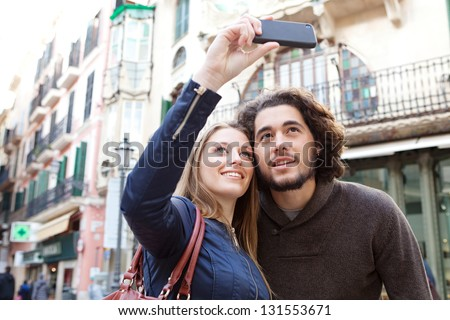 Close up portrait of a young tourist couple visiting a destination city and taking pictures of the classic buildings while on vacation in Europe
