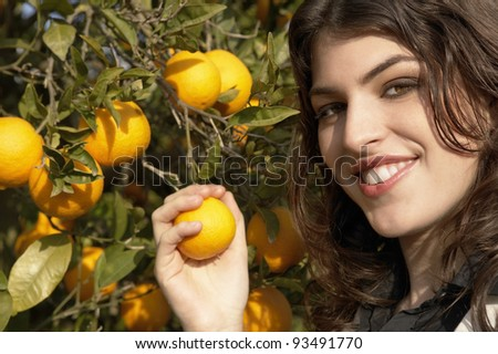 Close up portrait of a young woman holding an orange on a tree.