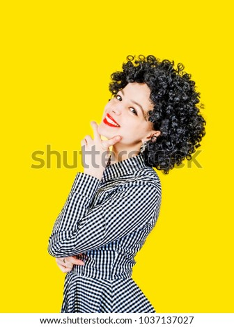 Close-up portrait of a young woman in an afro wig on a yellow background #1037137027