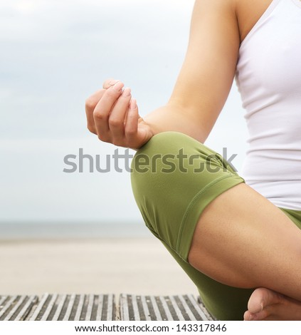 Close Up Portrait Of A Young Woman In Lotus Position With Yoga Hands At The Beach