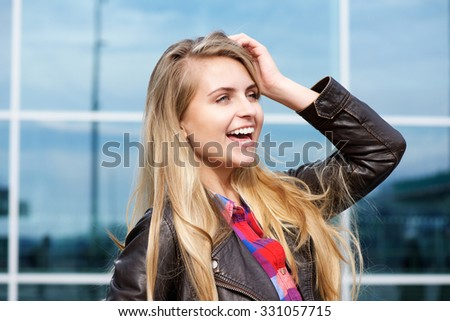 Close up portrait of a young woman laughing with hand in hair #331057715