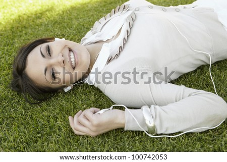 Close up portrait of a  young woman listening to music on her mp4, laying down on green grass in a park and smiling at camera.