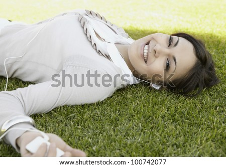 Close up portrait of a  young woman listening to music on her mp4, laying down on green grass in a park.
