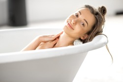 Close-up portrait of a young woman relaxing in the bathtube