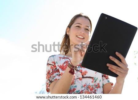 Close up portrait of a young woman using a digital tablet pad and touching the screen, standing against a blue sky during a sunny day.