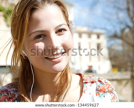 Close up portrait of a young woman using a smartphone to listen to music with her head phones, sitting outdoors in the city on a sunny day.