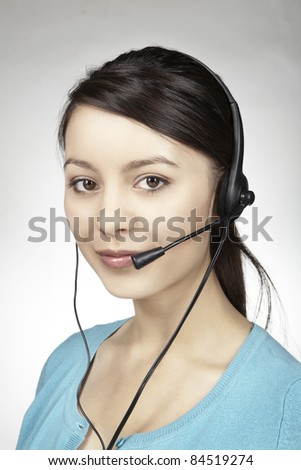 close up portrait of a young woman with a head set taking a call from some one