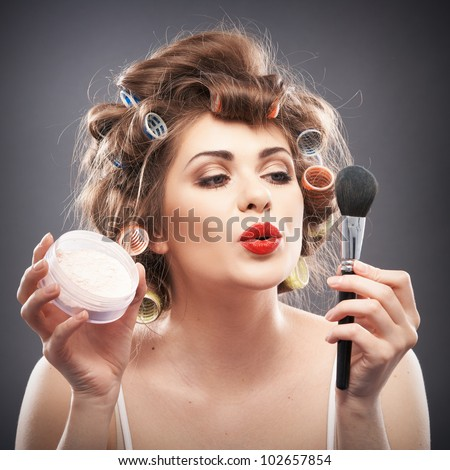 Close up portrait of a young woman with long hair on gray background making beauty face and hair style, applying powder at face. Smile happy girl  with make up accessories, studio isolated.