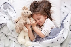 Close up portrait of adorable dark haired little girl calmly sleeping with sweet golden retriever pet in bedroom. Cute elementary age child resting on cozy bedding in nursery hugging her fluffy toys.