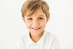 close-up portrait of adorable happy little boy smiling at camera isolated on white