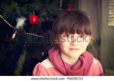 Close-up portrait of adorable little girl in front of Christmas tree