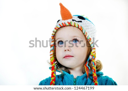 Close-up portrait of adorable smiling child girl wearing snowman knitted handmade hat