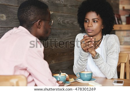 Close up portrait of African American friends at cafe having serious conversation, fashionable hipster woman with Afro hairstyle looking at her boyfriend with puzzled and thoughtful face expression #478301269