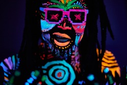 close-up portrait of african dj dancer with luminescent make-up and dreadlocks, wearing sunglasses. handsome guy isolated
