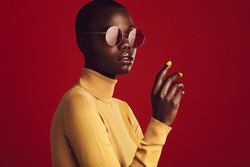 Close up portrait of african female with buzz cut hairstyle against red background. Beautiful african woman in casuals wearing sunglasses looking at camera.