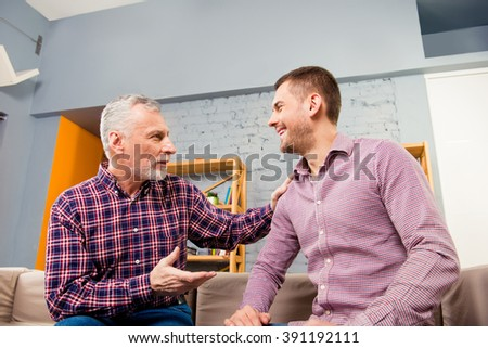 Close up portrait of aged father having talk with his adult son #391192111