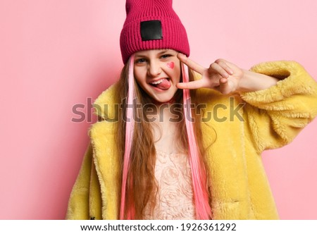Close up portrait of an active and cheerful teenage girl who is showing V-sign with her fingers and tongue. Little rebel in a pink hat, yellow fur coat posing on a pink background. Adolescence concept Stock photo ©