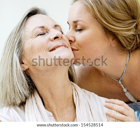 Close up portrait of an adult daughter kissing her mature mother on the cheek, being affectionate and smiling with joyful expressions while relaxing at home.
