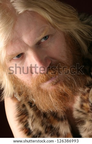 close-up portrait of an adult male with long hair, blonde, with a red beard and mustache, wearing a fur dress, looking in the direction of