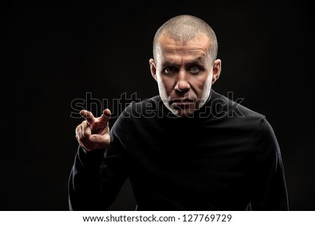 Close-up portrait of an aggressive man over black background. - stock photo