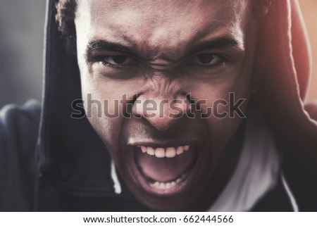 Close up portrait of an angry African American man wearing a hoodie and screaming in anger. Concept of strong emotions. Toned image #662444566