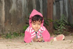 Close-up portrait of An Asian little baby boy child playing on sandy ground. Concept to childhood, beautiful indian child playing, Childhood memories.Beautiful baby portrait in nature . little boy .