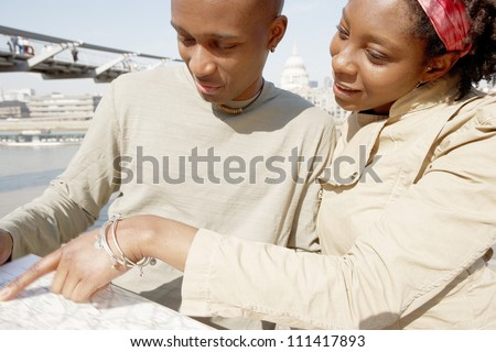 Close up portrait of an attractive black couple pointing at a guide map on vacation while standing by the Millennium Bridge and St Paul's Cathedral in London's river Thames.