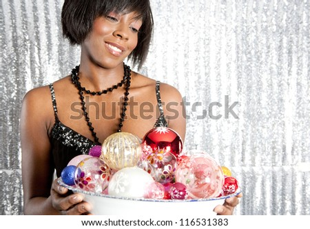 Close up portrait of an attractive black woman holding a dish full of christmas bar balls against a silver sequins background.