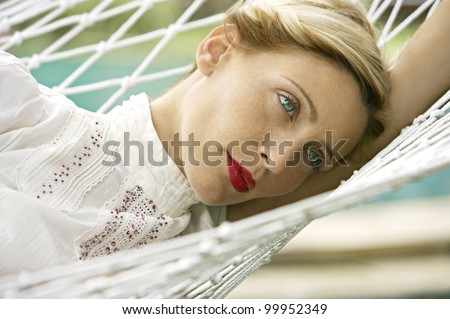 Close up portrait of an attractive blonde woman laying down on a hammock in a garden.
