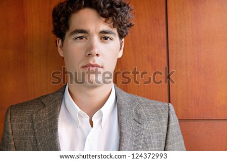 Close up portrait of an attractive businessman wearing an elegant suit and standing against a luxurious wooden wall, looking at the camera.