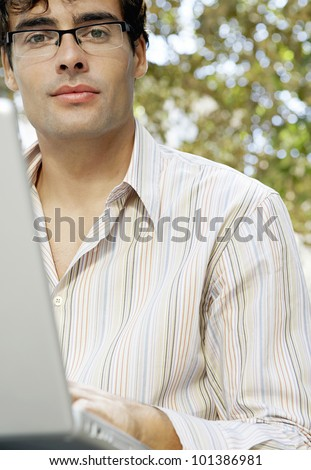 Close up portrait of an attractive businessman wearing glasses and using a laptop computer in the park.