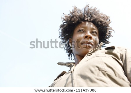 Close up portrait of an attractive young black woman against a blue sky, smiling.