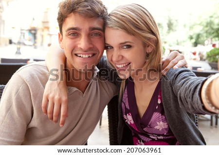 Close up portrait of an attractive young couple on holiday, taking selfies self portraits with a smartphone camera during a sunny day on vacation. Love and technology lifestyle, outdoors. - stock photo