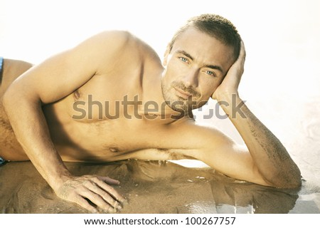 Close up portrait of an attractive young man laying down on a golden beach shore, smiling. - stock photo