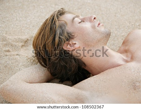 Close up portrait of an attractive young man sleeping on a golden sand beach.