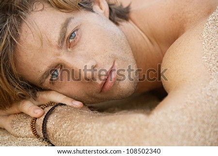 Close up portrait of an attractive young man sunbathing on the beach.
