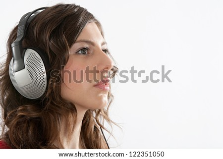 Close up portrait of an attractive young woman focused on listening to music on her headphones, isolated against a white background.