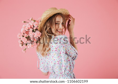 Close up portrait of an attractive young woman in summer dress and straw hat holding carnations bouquet and looking over her shoulder isolated over pink background