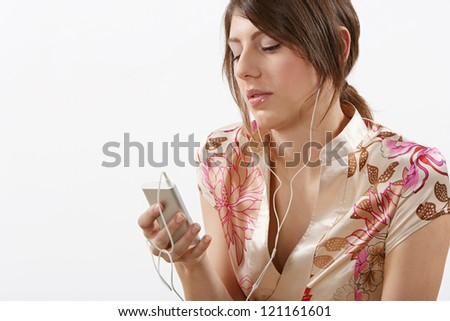 Close up portrait of an attractive young woman listening to music using her mp4 player and headphones, isolated against a while background.
