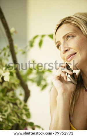Close up portrait of an attractive young woman using a cell phone in her home garden.