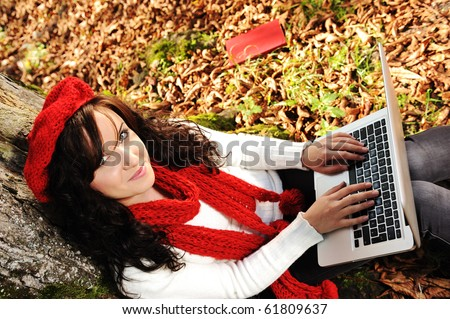 Close-up portrait of an beautiful autumn girl student working with laptop