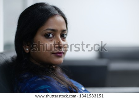 Close up portrait of an brunette Indian woman in blue traditional dress relaxing on the sofa of a waiting area inside an office. Indian lifestyle #1341583151
