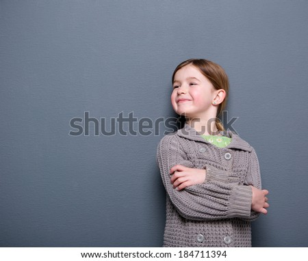 Close up portrait of an cute child of elementary age smiling with arms crossed on gray background