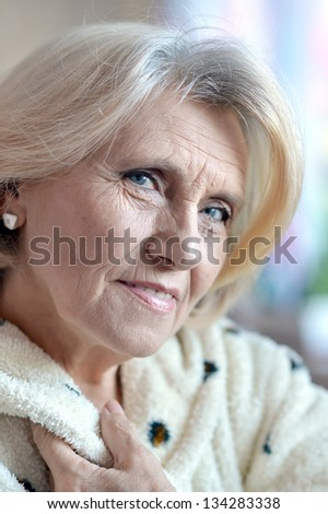 close-up portrait of an elderly woman in a bathrobe at home